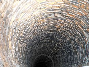 внутренняя поверхность промышленной трубы из кирпичной кладки со скобами для передвижения рабочих