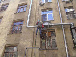 альпинист монтирует вентиляционную установку снаружи здания